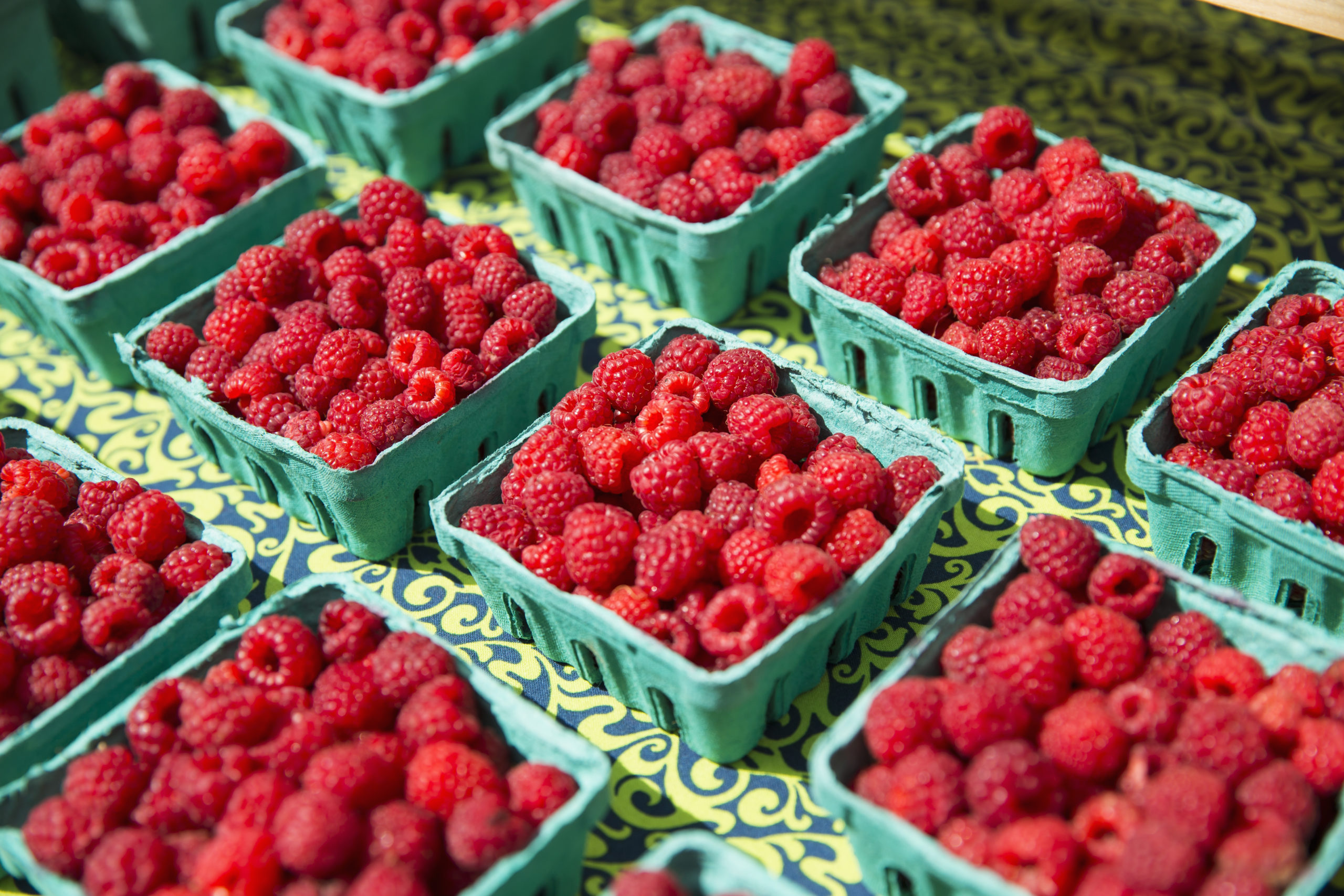 A farm stand, with displays of punnets of fresh berry fruits. Raspberries